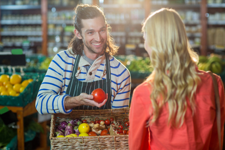 business lifestyle: Male staff assisting woman in selecting fresh vegetables in supermarket Stock Photo