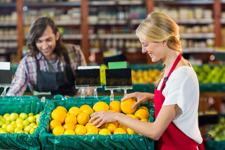 Smiling female staffs checking fruits in organic section of supermarket Stock Photo