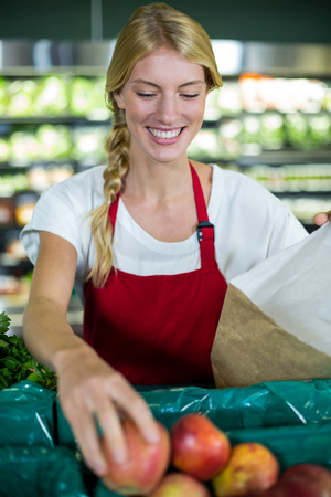 apple paper bag: Smiling female staff packing fruits in paper bag at supermarket
