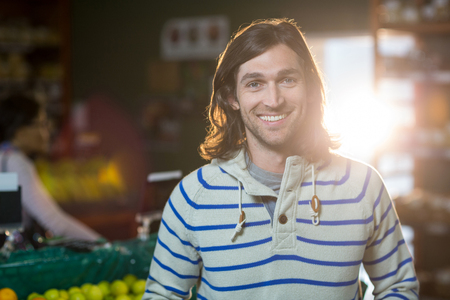 Portrait of smiling man standing in organic section of supermarket Stock Photo