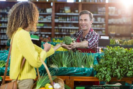 笑顔の男性スタッフが食料品のスーパー マーケットで買い物を女性を支援