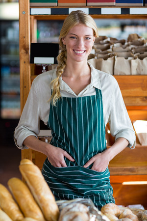 Portrait of smiling female staff standing at bread counter in supermarket Stock Photo