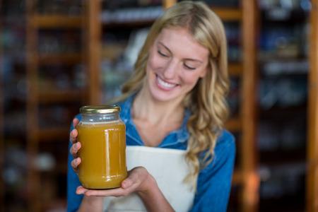 honey blonde: Smiling female staff holding jar of honey in supermarket