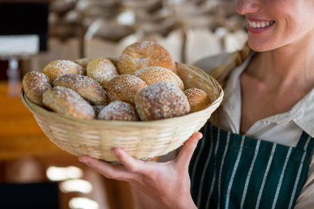 Mid section of smiling female staff holding basket of sesame breads at bread counter in supermarket