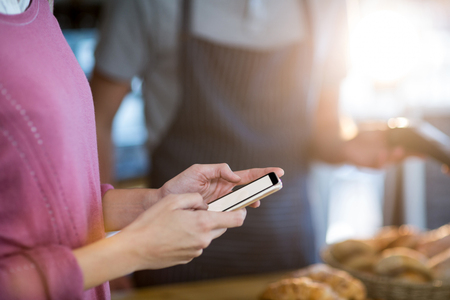 Mid-section of woman using mobile phone in café