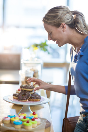 tempted: Excited woman selecting doughnuts from cake stand in café Stock Photo