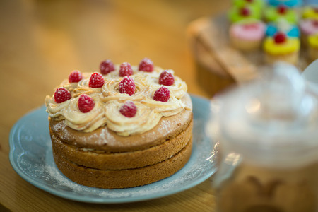 technology transaction: Sponge cake with whipped cream and cherry topping on plate in café