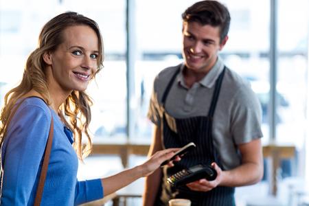 女性のスマート フォン カフェで NFC 技術を使用してを介して請求書の支払い 写真素材