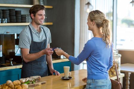 tomando refresco: dando la tarjeta de crédito del cliente feliz con el camarero en el café