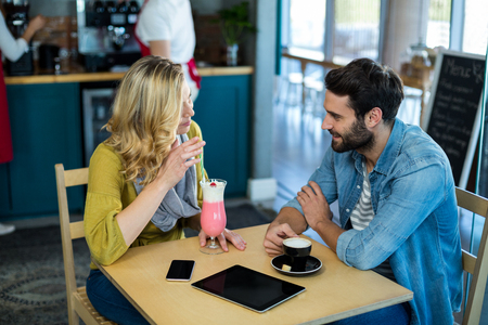 Couple interacting while having a cup of coffee and milkshake in café