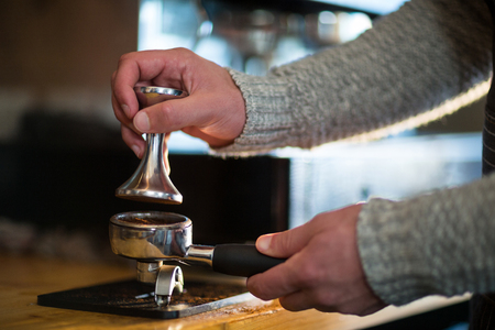 Waiter using a tamper to press ground coffee into a portafilter in café Stock Photo