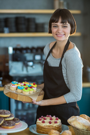 tempted: Portrait of smiling waitress holding cup cake on tray in café Stock Photo