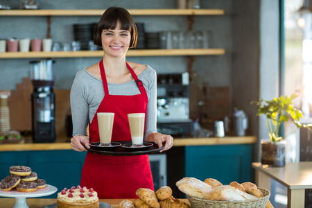 Portrait of waitress holding cup of cold coffee in café Stock Photo
