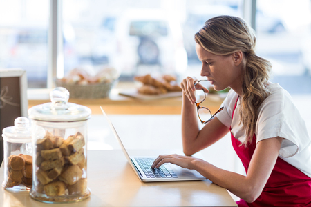Waitress sitting at table and using laptop in café
