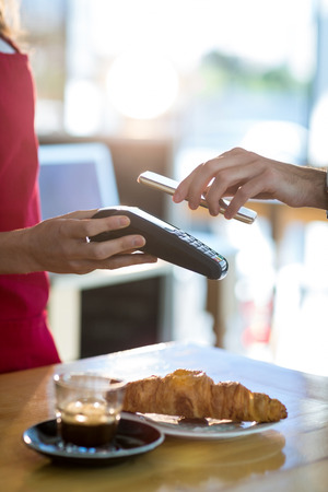 pin code: Man paying bill through smartphone using NFC technology in cafe