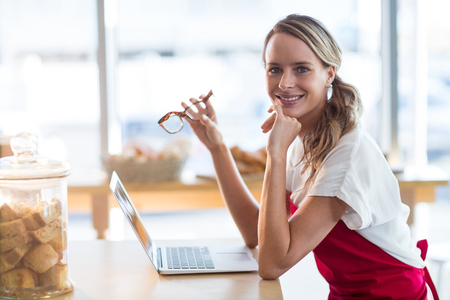 Portrait of smiling waitress sitting at table and using laptop in café