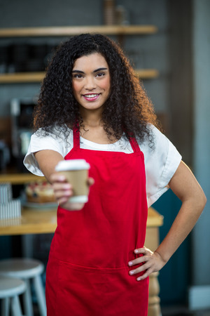 disposable cup: Portrait of waitress showing disposable cup of coffee