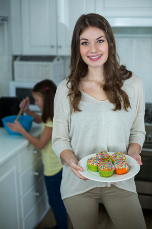 hundreds and thousands: Woman holding a plate of cupcakes in kitchen Stock Photo