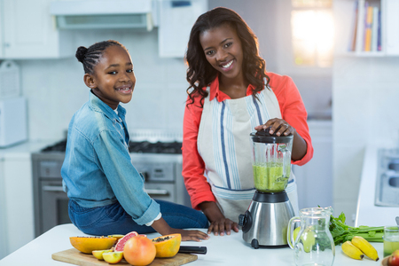 classy house: Woman and daughter using mixer in kitchen