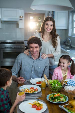 classy house: Happy family having breakfast in kitchen Stock Photo