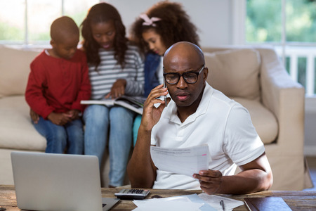 classy house: Man talking on mobile phone while checking bills at home