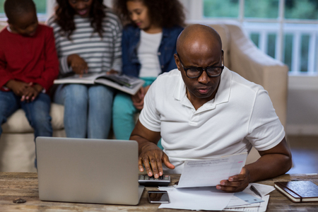 hp: Man using calculator to check the bills at home Stock Photo
