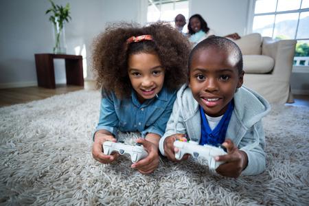 niños jugando videojuegos: Los niños que juegan juegos de video en casa