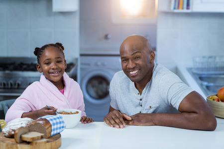 classy house: Portrait of father and daughter having breakfast in kitchen