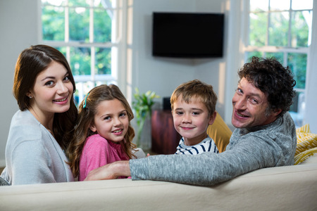 family sofa: Portrait of family sitting on sofa at home Stock Photo