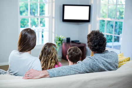 family sofa: Family watching television while sitting on sofa at home