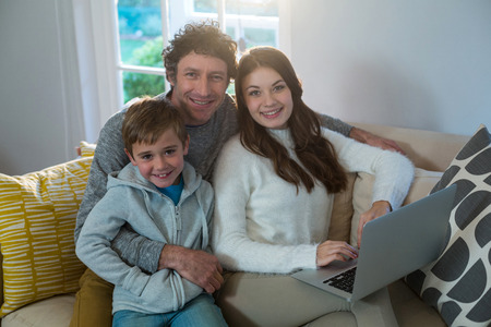 family sofa: Family using laptop on sofa at home