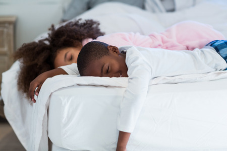 Children sleeping on bed at home