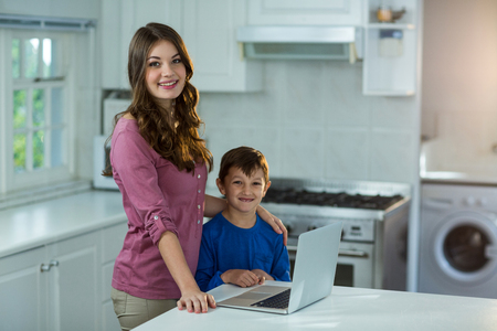 classy house: Mother and son with laptop at kitchen