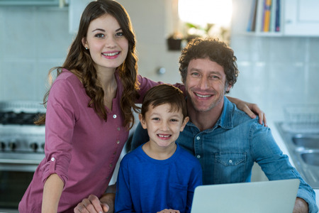 Portrait of family using laptop at kitchen Stock Photo