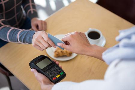 tomando refresco: Cliente que da la tarjeta de crédito al camarero en la cafetería