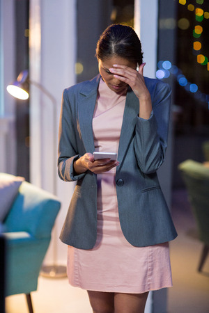 Tensed businesswoman using mobile phone in office at night Stock Photo