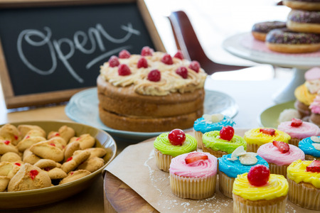 food drink industry: Close-up of various sweet foods on table with open signboard in cafeteria Stock Photo