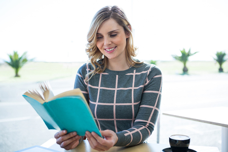 novel: Smiling woman reading novel in cafeteria