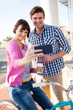 tomando refresco: Happy couple with coffee cups taking a selfie Foto de archivo