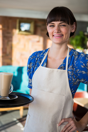 Portrait of smiling waitress holding a glass of coffee in the coffee shop