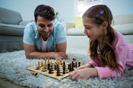 pawn adult: Father and daughter playing chess in the living room at home