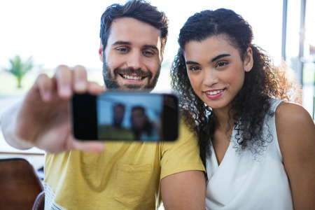 Smiling couple taking a selfie in coffee shop Stock Photo