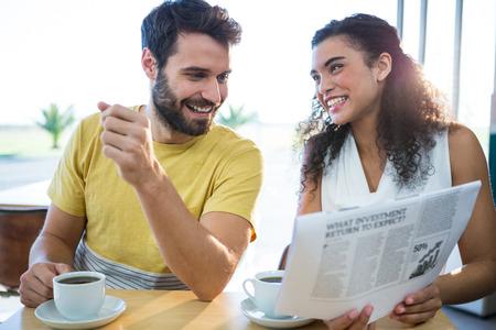 Sourire couple journal de lecture tout en ayant le café dans un café