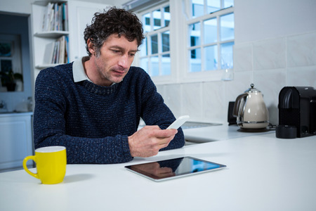 Portrait of man using mobile phone in the kitchen at home