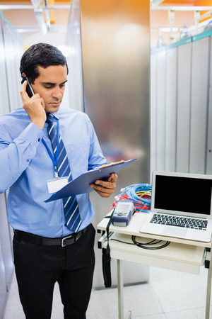 Technician dictating checklist report on mobile phone in server room Stock Photo