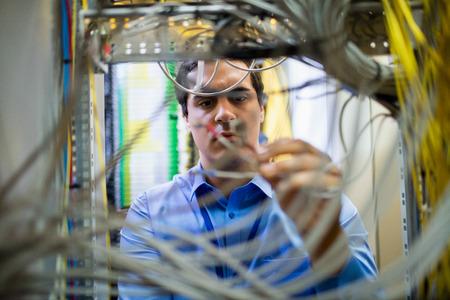attentive: Attentive technician fixing cable in server room