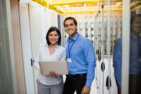 Portrait of technicians using laptop in server room Stock Photo