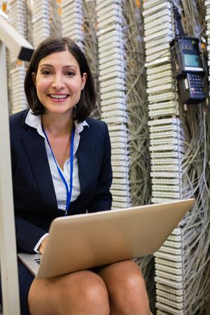 Portrait of happy technician using laptop in server room