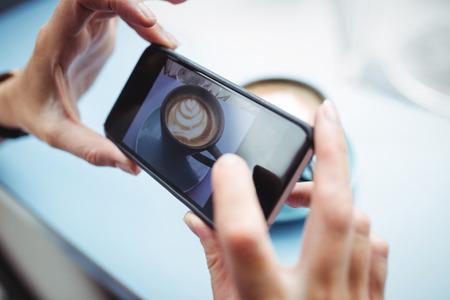 tomando refresco: Mujer que toma la foto de un café desde el teléfono móvil en la oficina