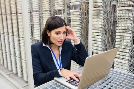 tensed: Tensed technician using laptop in server room